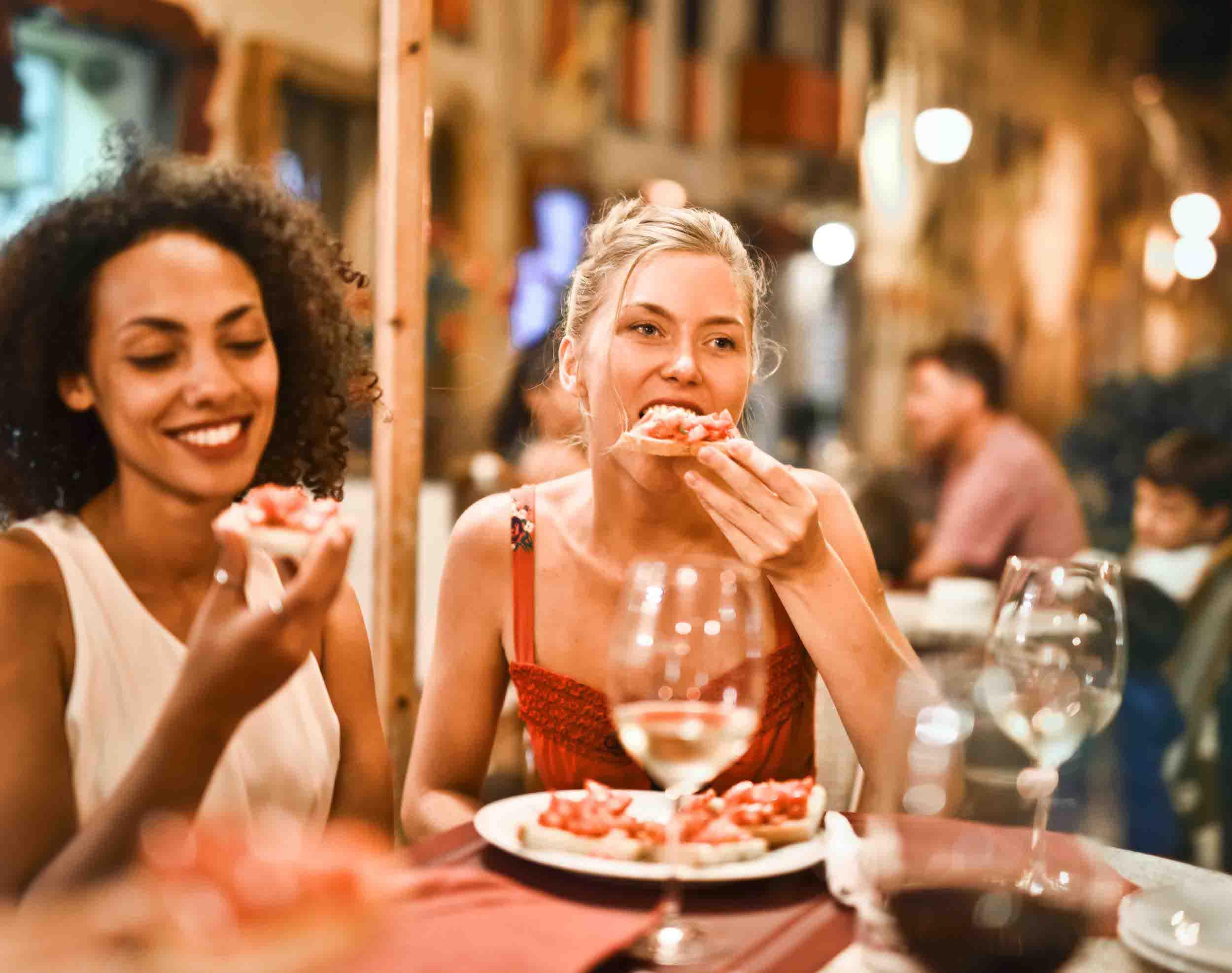 beautiful girls eating and enjoying food at restaurant